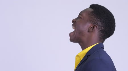 guinean : Closeup profile view of angry young African businessman shouting