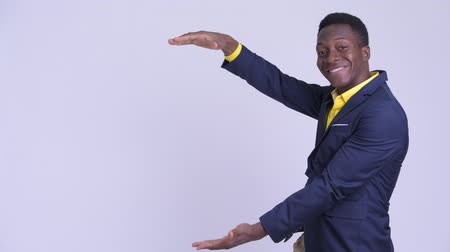 guinean : Young happy African businessman snapping fingers and showing something Stock Footage