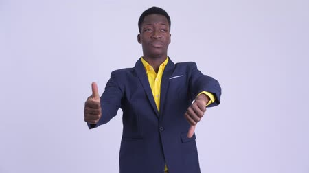 guinean : Young confused African businessman choosing between thumbs up and thumbs down