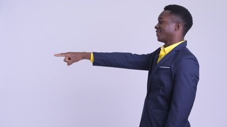 přímý : Profile view of young happy African businessman pointing finger