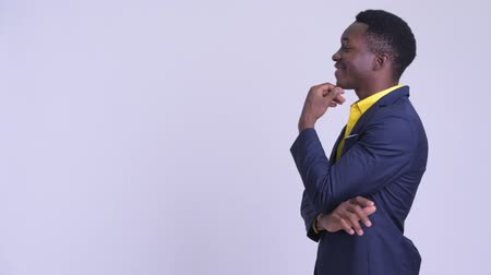 задумчивый : Profile view of young happy African businessman thinking