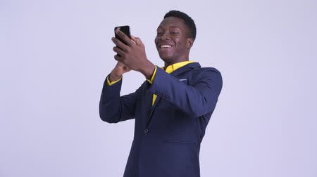 guinean : Young happy African businessman video calling with phone Stock Footage
