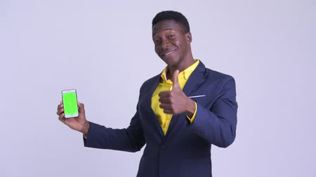 guinean : Young happy African businessman showing phone and giving thumbs up