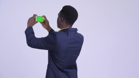 guinean : Rear view of young happy African businessman taking picture with phone Stock Footage