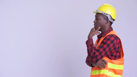 guinean : Profile view of happy young African man construction worker thinking Stock Footage