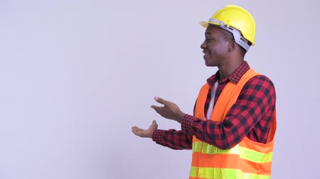 guinean : Young happy African man construction worker showing something to the back