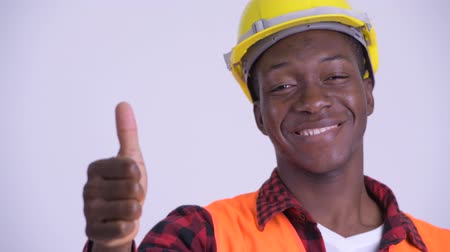 guinean : Face of young happy African man construction worker giving thumbs up