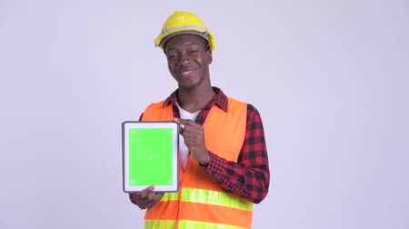 guinean : Young happy African man construction worker showing digital tablet