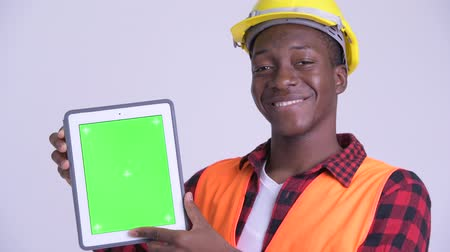 guinean : Face of young happy African man construction worker showing digital tablet