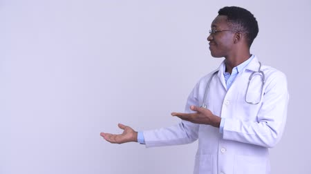 guinean : Young happy African man doctor showing something