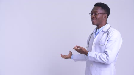 guinean : Young happy African man doctor showing something to the back
