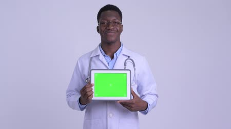guinean : Young happy African man doctor showing digital tablet
