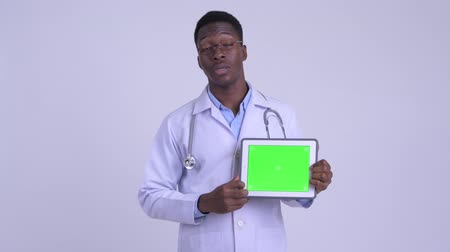 guinean : Young happy African man doctor talking while showing digital tablet