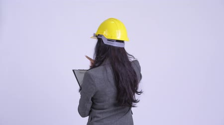 direto : Rear view of Persian businesswoman as engineer directing while holding clipboard