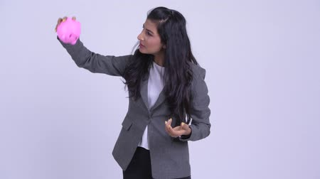 meteliksiz : Young stressed Persian businesswoman shaking piggy bank and giving thumbs down Stok Video