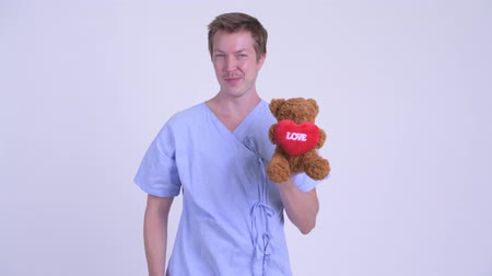 éretlen : Happy young man patient holding teddy bear and acting childlike