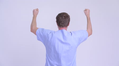 raising fist : Rear view of happy young man patient with fists raised Stock Footage