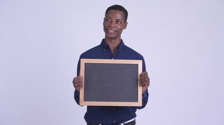 guinean : Young happy African businessman holding blackboard