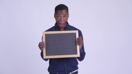 guinean : Young happy African businessman holding blackboard and looking surprised Stock Footage