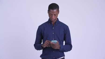 guinean : Young happy African businessman thinking while using phone