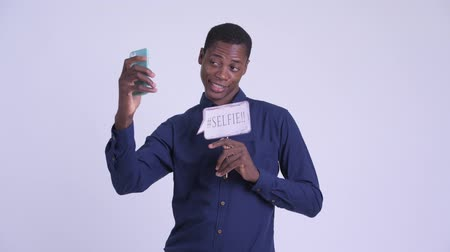 guinean : Young happy African businessman taking selfie with paper sign Stock Footage