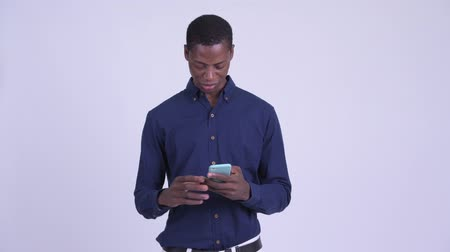 guinean : Young stressed African businessman using phone and getting bad news
