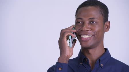 guinean : Face of young happy African businessman talking on the phone