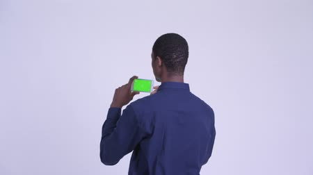 vlogging : Rear view of young happy African businessman taking picture with phone Stock Footage