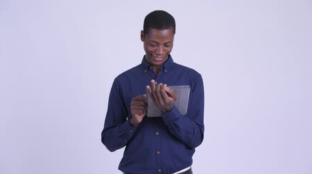 guinean : Young happy African businessman using digital tablet
