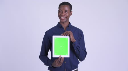 guinean : Young happy African businessman thinking while showing digital tablet