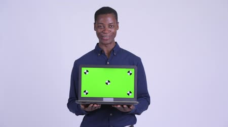 guinean : Young happy African businessman showing laptop and looking surprised Stock Footage