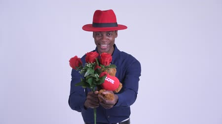 guinean : Young happy African businessman giving gifts ready for Valentines day