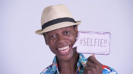 guinean : Face of young happy African tourist man smiling with selfie paper sign
