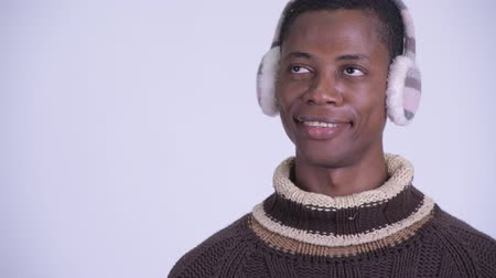 earmuff : Face of young happy African man thinking ready for winter Stock Footage