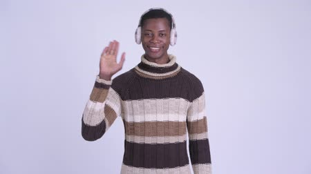earmuff : Young happy African man waving hand ready for winter