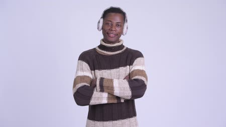earmuff : Young happy African man smiling with arms crossed ready for winter Stock Footage
