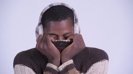earmuff : Face of young African man covering face and feeling cold for winter