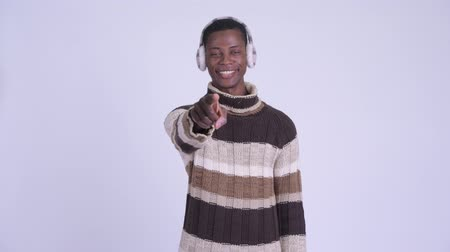 earmuff : Young happy African man pointing at camera ready for winter