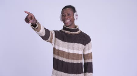 earmuff : Young happy African man pointing finger ready for winter Stock Footage