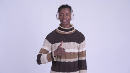 earmuff : Young happy African man giving thumbs up ready for winter