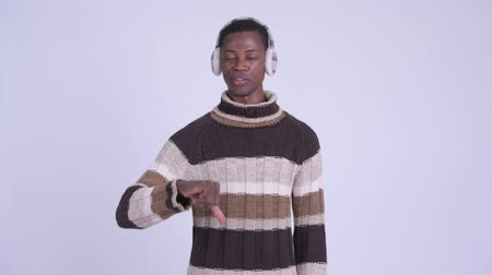 earmuff : Young stressed African man giving thumbs down for winter