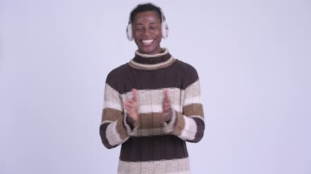 earmuff : Young happy African man clapping hands ready for winter Stock Footage