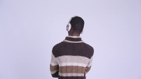 earmuff : Rear view of young African man pointing finger ready for winter