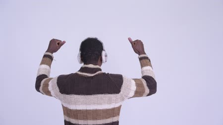 raising fist : Rear view of young happy African man with fists raised ready for winter