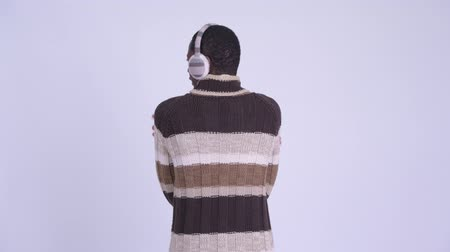 earmuff : Rear view of young African man waiting and thinking ready for winter Stock Footage