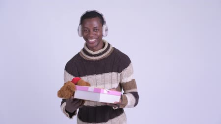 earmuff : Young happy African man getting gifts for Christmas day
