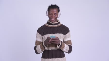 earmuff : Young happy African man thinking while using phone ready for winter Stock Footage