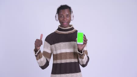 earmuff : Young happy African man showing phone and giving thumbs up ready for winter