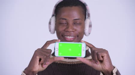 earmuff : Face of young happy African man showing phone ready for winter Stock Footage