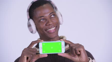 guinean : Face of young happy African man thinking while showing phone ready for winter Stock Footage
